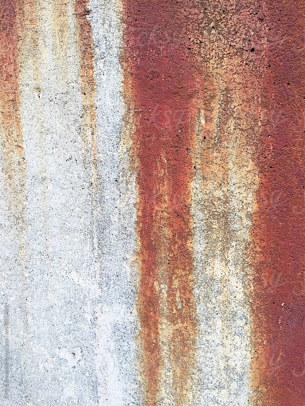 Dripping rust marks on concrete wall, close up by Paul Edmondson for Stocksy United
