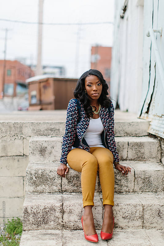 Trendy and fashionable african-american woman sitting on concrete steps by an abandoned building by Jakob for Stocksy United