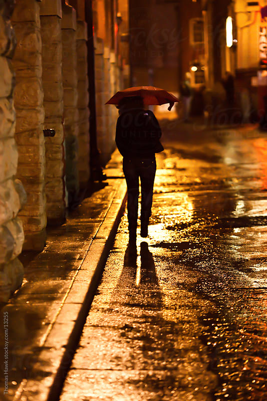 A silhouette of a woman walking in the rain at night in Nashville, TN by Thomas Hawk for Stocksy United
