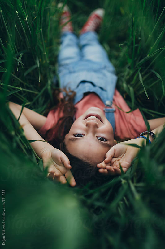 Smiling little girl lying in lawn. by Dejan Ristovski for Stocksy United