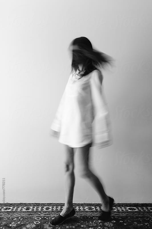 Black and White movement shot of woman wearing a long shirt by Jacqui Miller for Stocksy United