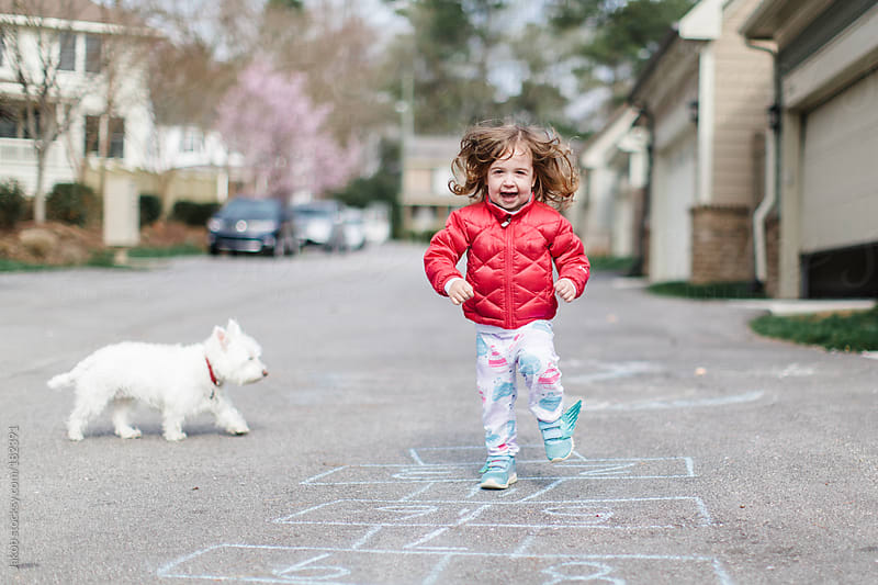 Cute toddler doing hopscotch outside by Jakob for Stocksy United