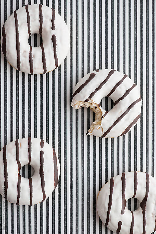 Food: Black and white striped Donuts on striped background by Ina Peters for Stocksy United