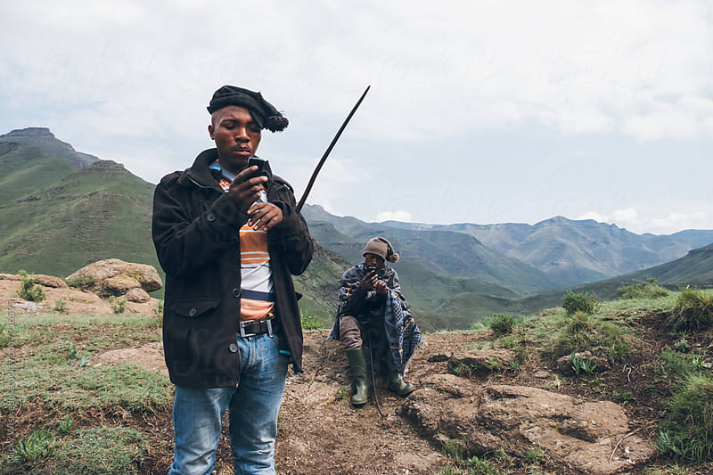 Basotho herdsmen using mobile phones in the Lesotho mountains by Micky Wiswedel for Stocksy United