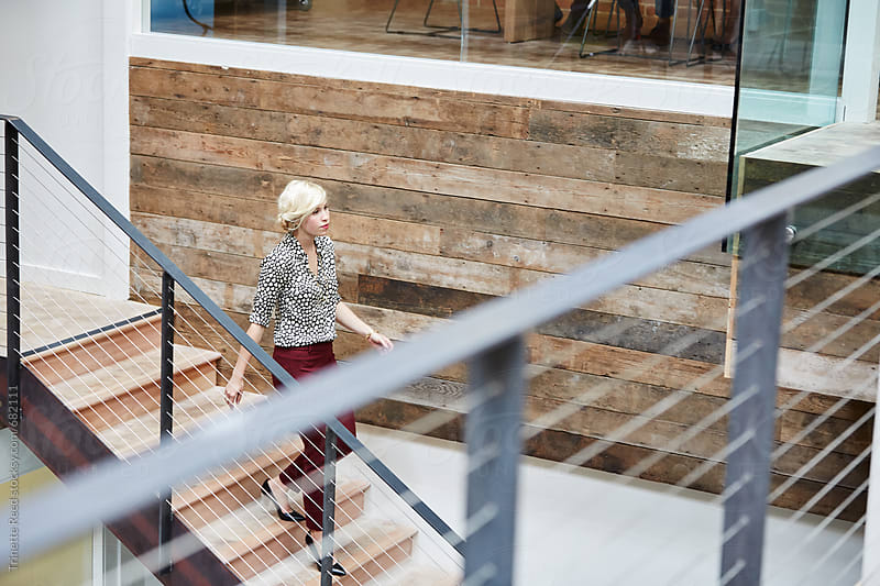 Millennial businesswoman at office walking down stairs by Trinette Reed for Stocksy United