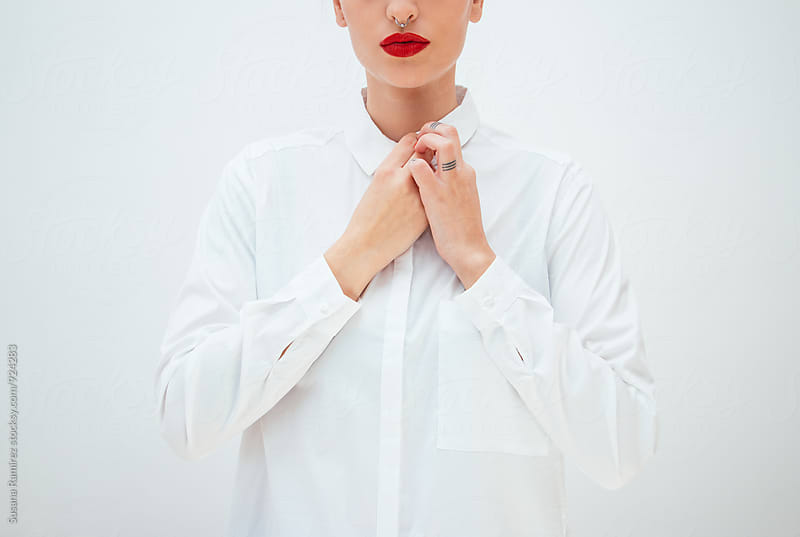 Woman buttoning shirt by Susana Ramírez for Stocksy United