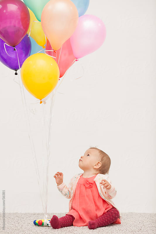 Cute little baby girl playing with colorful balloons at home. by Mosuno for Stocksy United
