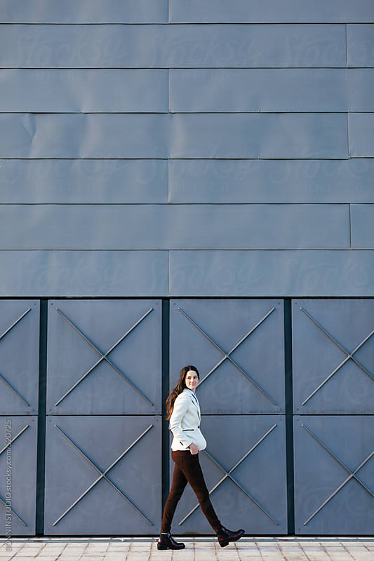 Young businesswoman walking on the street. by BONNINSTUDIO for Stocksy United
