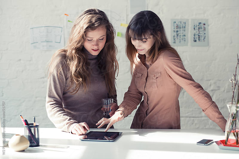 Two young executives working with a tablet PC. by W2 Photography for Stocksy United