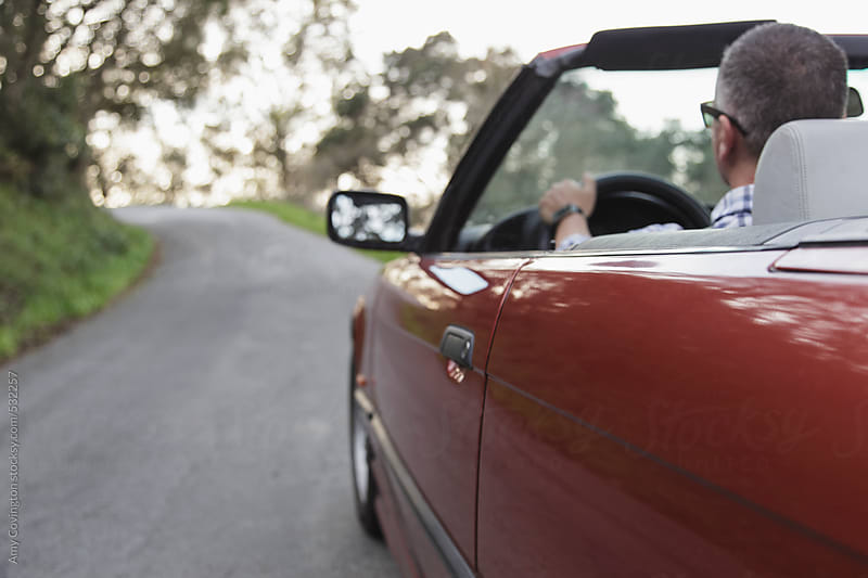 Man driving in a convertible car by Amy Covington for Stocksy United
