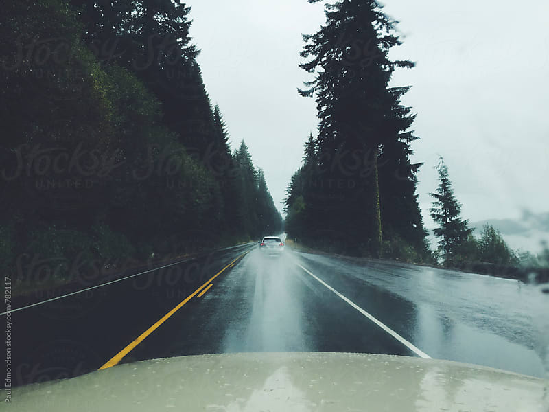 View through car windshield of road and wet weather by Paul Edmondson for Stocksy United