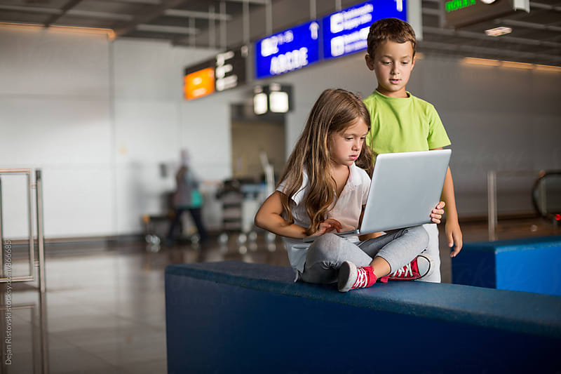 Children in a waiting room at the airport. by Dejan Ristovski for Stocksy United