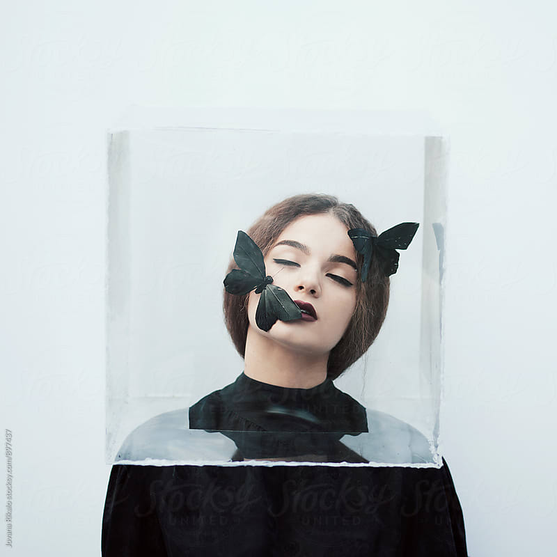 Artistic portrait of a young woman with a box on her head