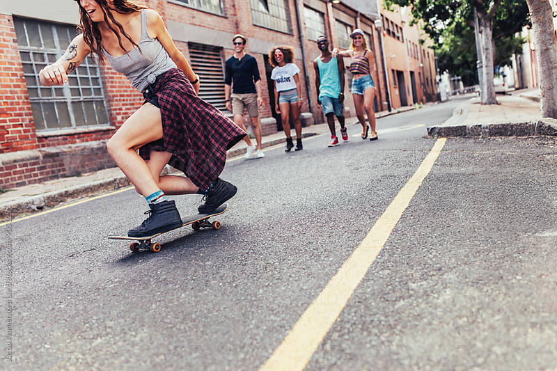 Young girl skateboarding with group of people walking by Jacob Ammentorp Lund for Stocksy United