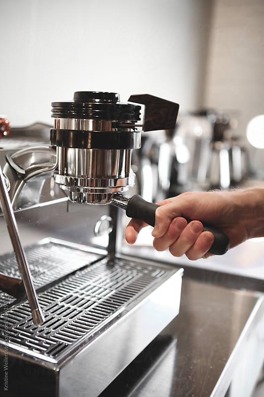 Hand putting portafilter on espresso machine by Kristine Weilert for Stocksy United