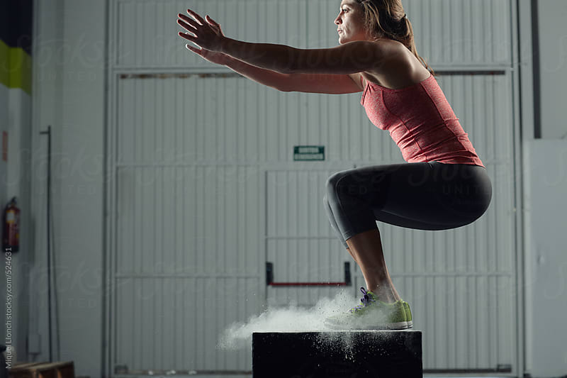 Fit woman jumping on a workout box by Miquel Llonch for Stocksy United