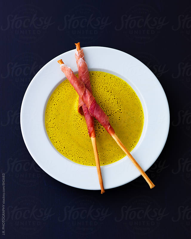 Curried courgette soup, grissini wrapped in prosciutto by J.R. PHOTOGRAPHY for Stocksy United