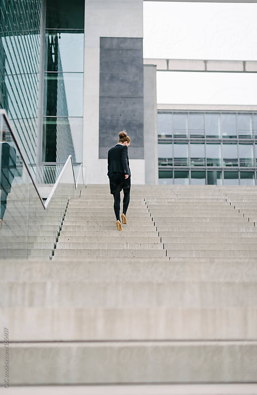 Businesswoman walking on the steps of a big company by GIC for Stocksy United