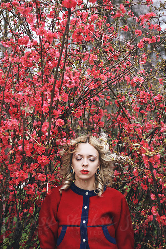 Young woman standing with closed eyes amongst red flowers by Jovana Rikalo for Stocksy United