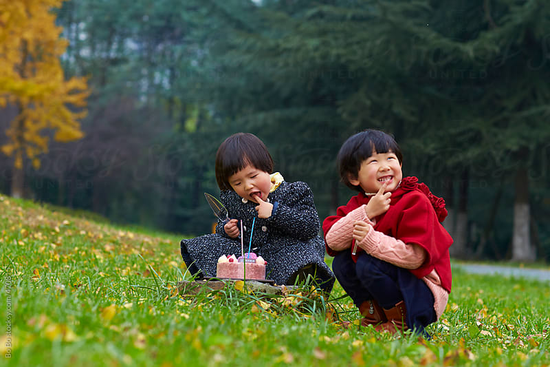 two little girls eating birthday cake in the park by Bo Bo for Stocksy United