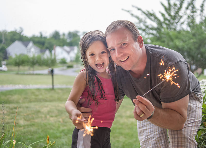 Little girl with father holding sparklers by Brian McEntire for Stocksy United