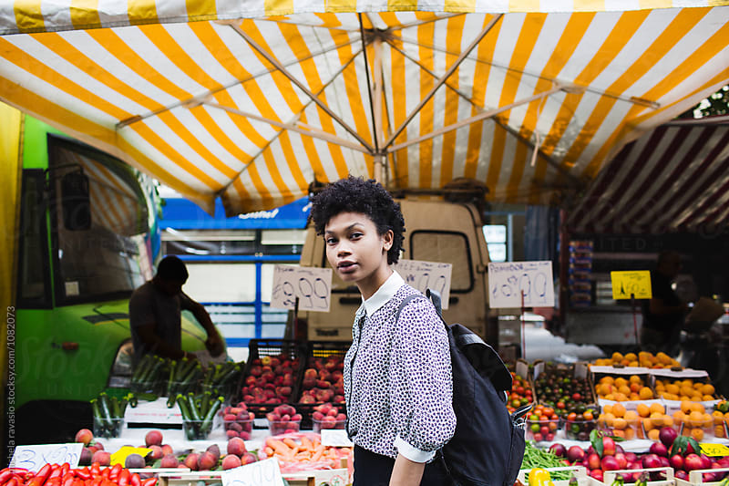 Young woman walks into a local fruit and vegetable market by michela ravasio for Stocksy United