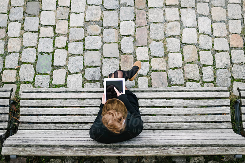 Young businesswoman using a digital tablet sitting on a bench by GIC for Stocksy United