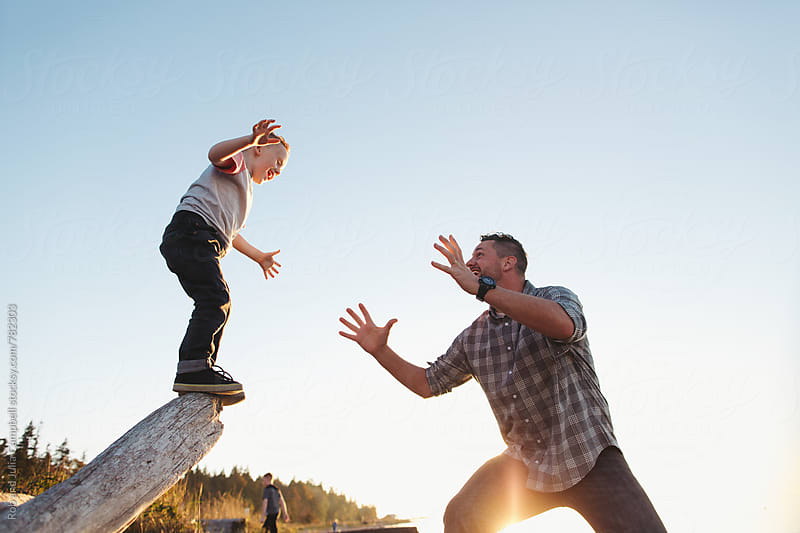 Energetic dad playing with son at sunset near water - kid jumping off log by Rob and Julia Campbell for Stocksy United