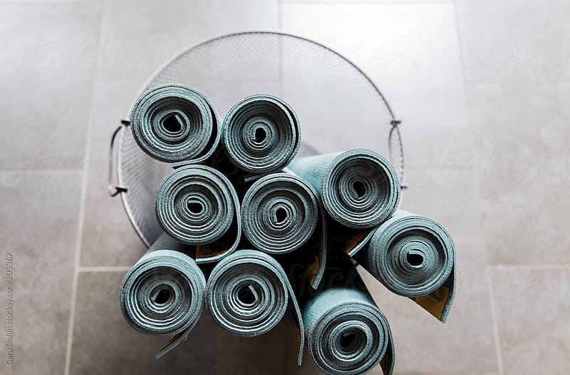 Yoga mats rolled up in a metal basket by Cara Dolan for Stocksy United