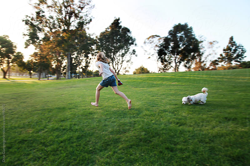 Little girl running with dog in park by Dina Giangregorio for Stocksy United