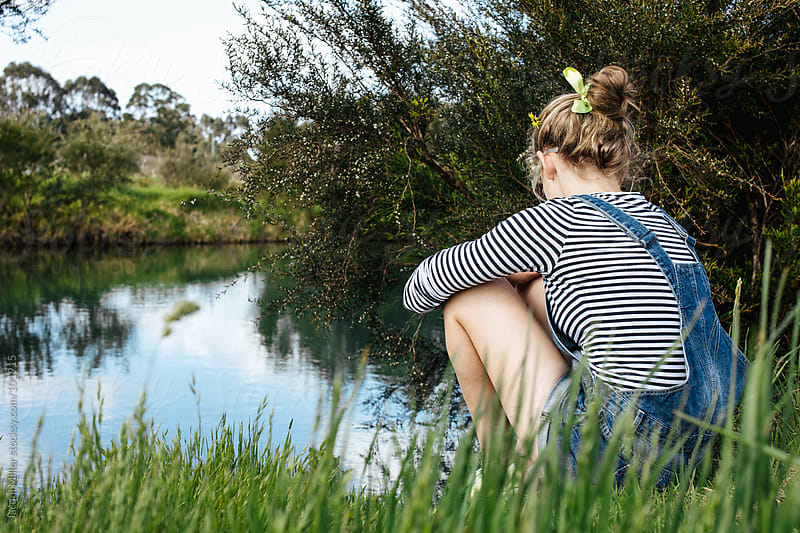 Teenage girl sits beside a farm Dam by Jacqui Miller for Stocksy United