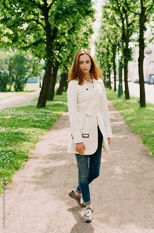 Young woman posing at a green alley by Lyuba Burakova for Stocksy United