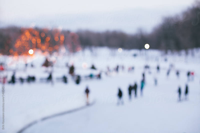 Out of focus people skating on a frozen lake by Erik Naumann for Stocksy United