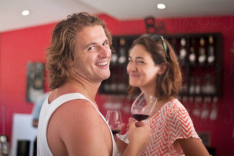 young couple at a cellar door, tasting wine by Gillian Vann for Stocksy United