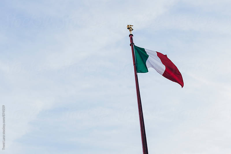Italian flag weaving against of cloudy sky by Trent Lanz for Stocksy United