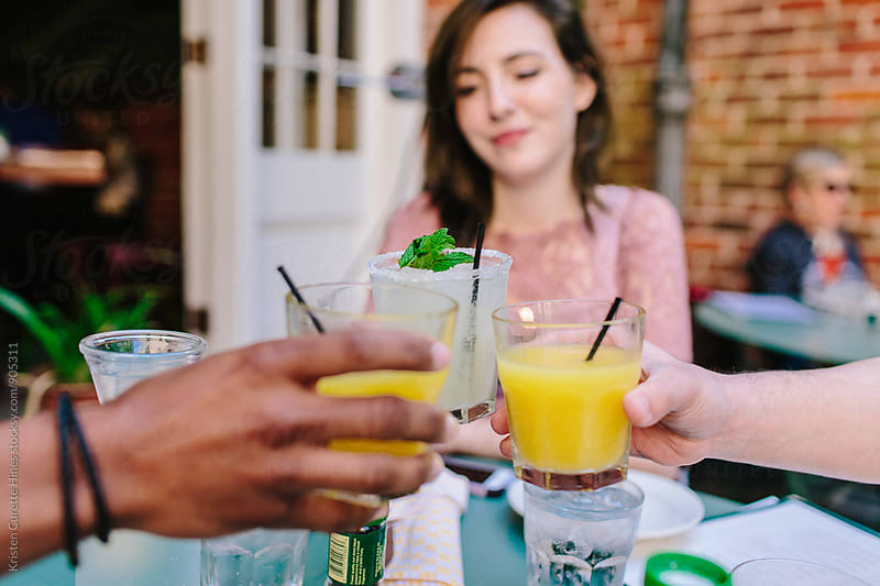 Friends toasting glasses at an outdoor patio during brunch by Kristen Curette Hines for Stocksy United