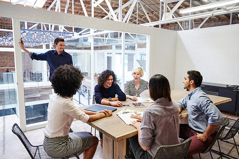Group of millennials in meeting in boardroom by Trinette Reed for Stocksy United