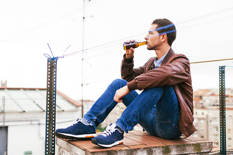 Young male drinking beer sitting on a rooftop. by BONNINSTUDIO for Stocksy United