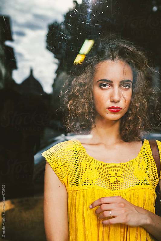 Yellow Dressed Young Woman Watching Through the Glass of a Window by Giorgio Magini for Stocksy United