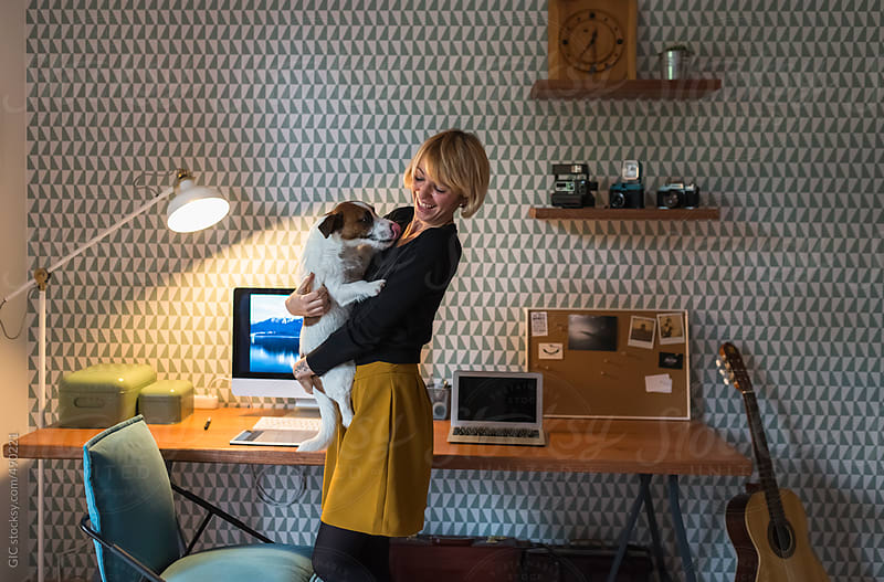 Woman playing with her dog in the office at home by GIC for Stocksy United