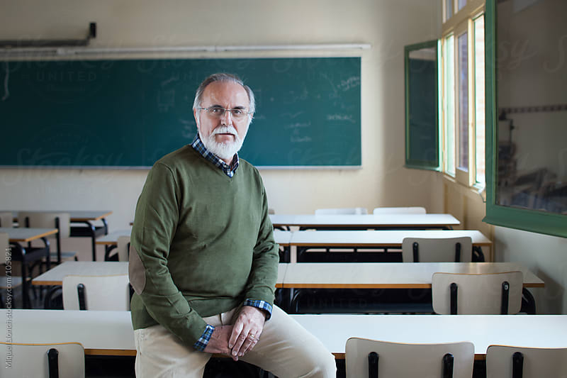 Portrait of a mature professor in a classroom by Miquel Llonch for Stocksy United