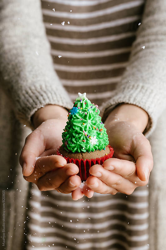 Woman holding christmas cupcake by MaaHoo Studio for Stocksy United