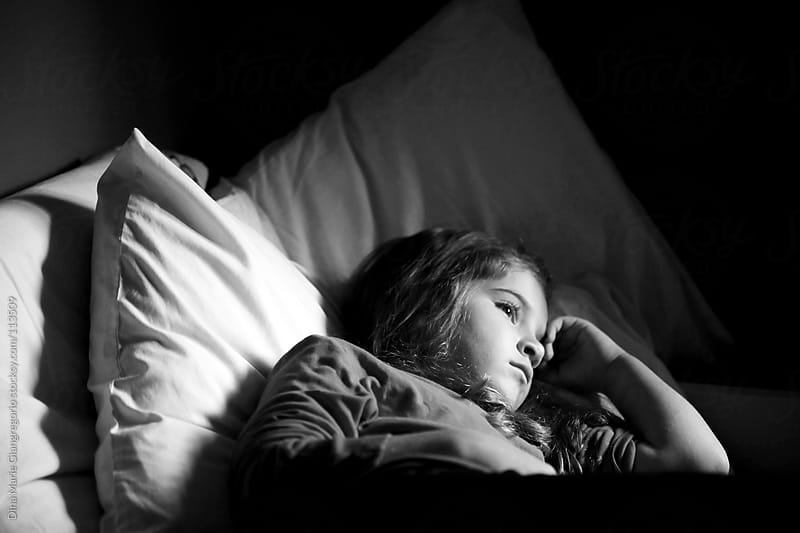Sad young girl laying in bed by Dina Giangregorio for Stocksy United
