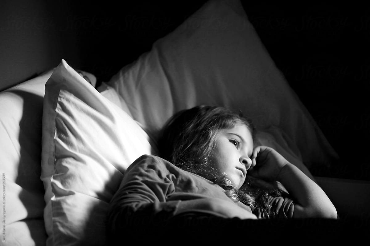 sad young girl laying in bed stocksy united. Black Bedroom Furniture Sets. Home Design Ideas