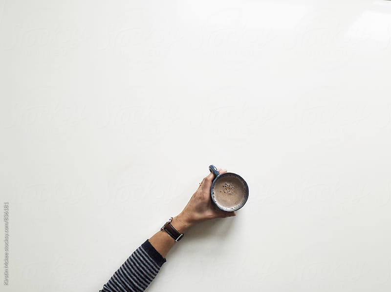 Overhead image of someone holding a cup of tea.  by Kirstin Mckee for Stocksy United