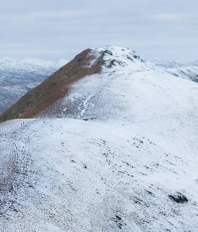 Hikers make their way up a snowy mountain path on the Ben Ledi mountain. by Andy Campbell for Stocksy United