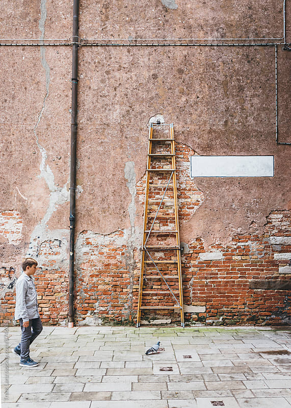 Kid walking on street with a bird against brick wall in Venice  by Trent Lanz for Stocksy United
