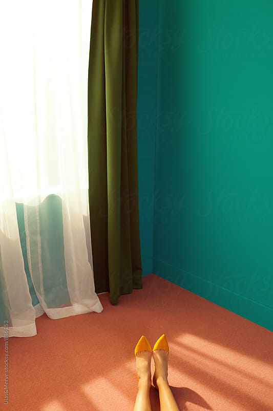 legs of a lady with high heels in colorful room by Ulaş and Merve for Stocksy United