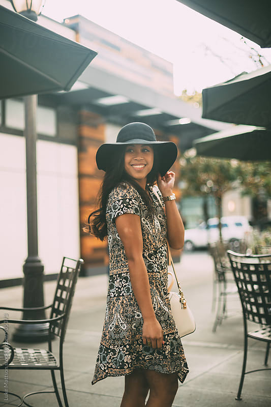 Smiling Young Woman In Dress And Sun Hat by Luke Mattson for Stocksy United