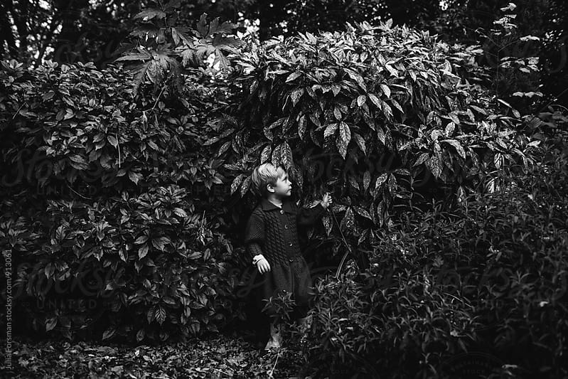Small girl next to tall foliage. by Julia Forsman for Stocksy United